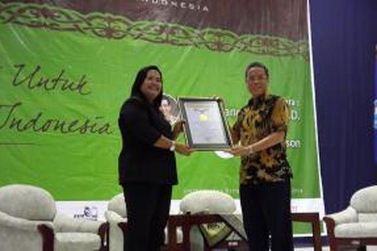 Tampak dalam gambar Direktur SDM PT Indocement Tunggal Prakarsa Tbk., Kuky Permana menerima piagam rekor MURI dari Manajer MURI, Ida, Sabtu (14/6/2014).