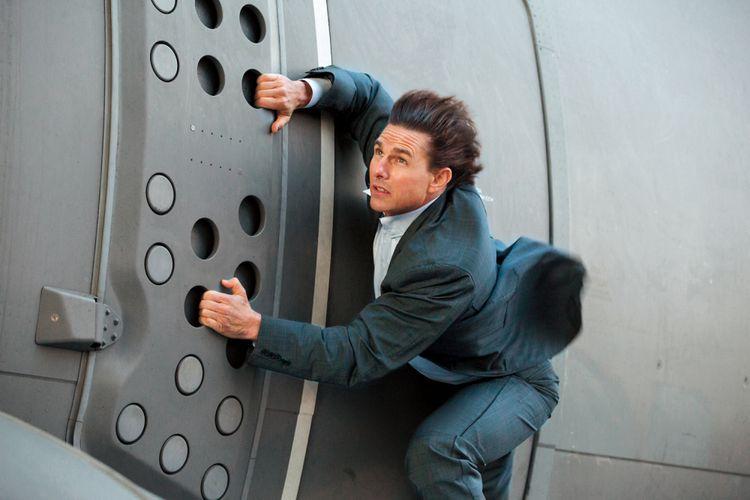 Aktor Tom Cruise berpegangan pada sisi sebuah pesawat yang hendak lepas landas dalam film Mission: Impossible - Rogue Nation.