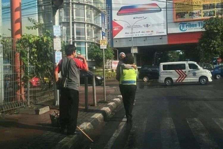 Anggota Satuan Lalulintas Polrestabes Makassar, Aiptu Chaterina Yani menggendong nenek yang kelelahan.