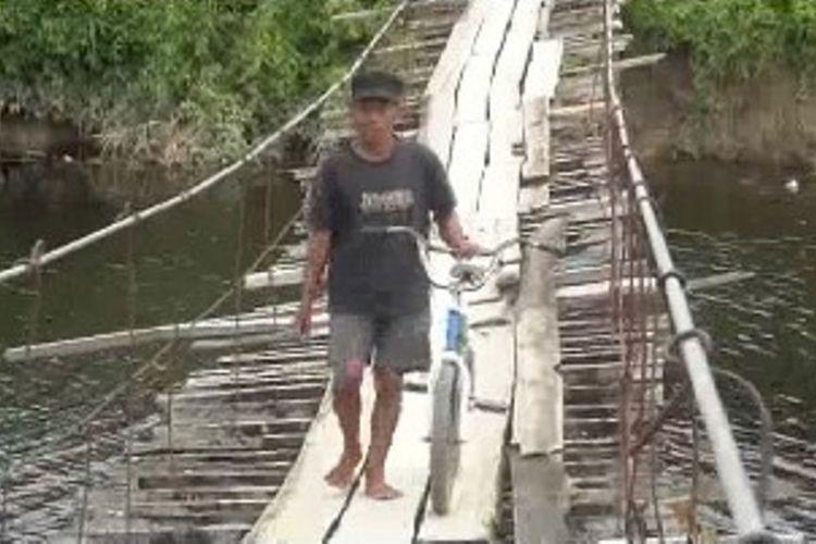 Meski dihadang kawanan buaya raksasa, warga Pasangkayu, Sulawesi Barat, nekat bertaruh nyawa melintasi jembatan gantung saat kawanan buaya tengah lalu lalang di bawah bentangan jembatan.