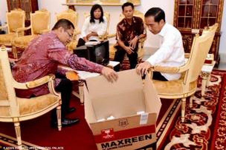 Kusrin menunjukkan TV hasil karyanya yang diberi merk MAXREEN kepada Presiden Joko Widodo di Istana Merdeka, Senin (25/1/2016).