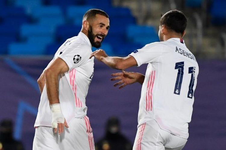 Karim Benzema (kiri) merayakan golnya bersama Marco Asensio (kanan) pada laga ketiga Grup B Liga Champions yang mempertemukan Real Madrid vs Iner Milan di Stadion Alfredo Di Stefano, Rabu (4/11/2020) dini hari WIB.