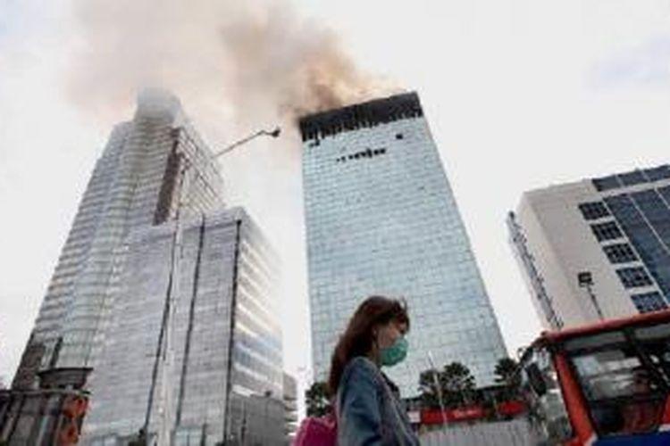 Pekerja melintas di dekat gedung Wisma Kosgoro di Jalan MH Thamrin, Jakarta Pusat, yang masih terbakar, Selasa (10/3) pagi. Petugas pemadam kebakaran terus berupaya memadamkan api di gedung itu. Kebakaran mulai terjadi Senin (9/3) petang.