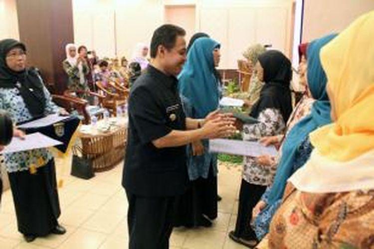 Nur Mahmudi Ismail menyerahkan bantuan posyandu.