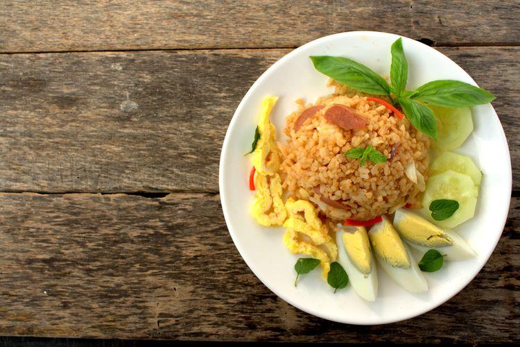 Ilustrasi nasi goreng dengan topping telur dadar, telur rebus, timun, dan daun kemangi.