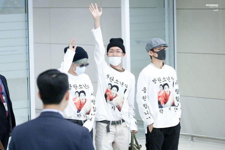 Tiga member BTS, (dari kiri) Jimin, J-Hope, dan V memamerkan kaus istimewa saat tiba di Bandara Incheon, Seoul, Korea Selatan, Rabu (24/10/2018).