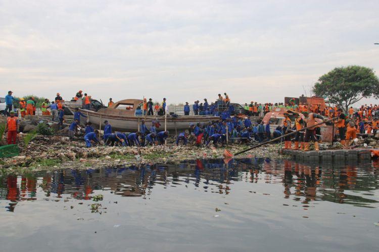 Petugas melakukan pembersihan sampah di pesisir Marunda Kepu, Cilincing, Minggu (10/3/2019).