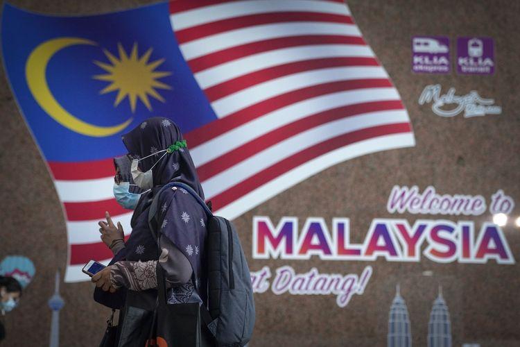 Dua wanita memakai masker untuk mencegah penyebaran virus corona, saat berjalan di stasiun kereta api Kuala Lumpur, Malaysia, 12 Oktober 2020.