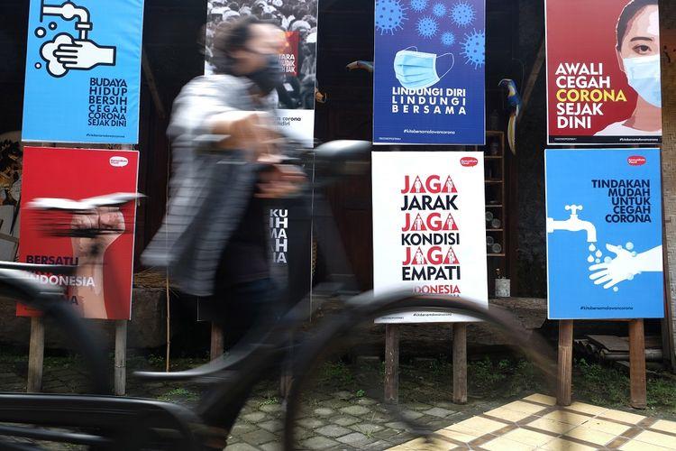 Warga melintas di depan poster bertajuk Desain Poster untuk Indonesia Bersama Lawan Corona yang dipajang di halaman Roemah Rakyat, Banjarsari, Solo, Jawa Tengah, Rabu (1/4/2020). Desain poster yang juga dipamerkan di sosial media tersebut dibuat sebagai media informasi, edukasi, sekaligus pemantik spirit kebersamaan untuk bangsa Indonesia bersatu padu melawan virus COVID-19. ANTARA FOTO/Maulana Surya/hp.