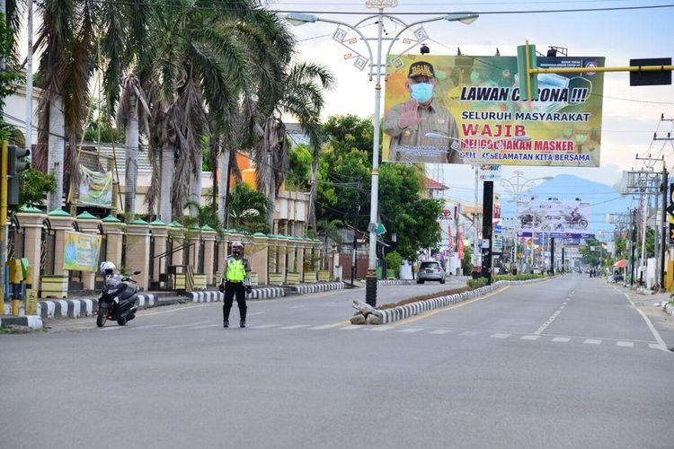 Situasi jalan Nani Wartabone pada hari pertama pemberlakuan Pembatasan Sosial Berskala Besar (PSBB) yang terlihat lengang. Seorang polisi lalu lintas sedang berjaga-jaga di depan Masjid Baiturrahim.