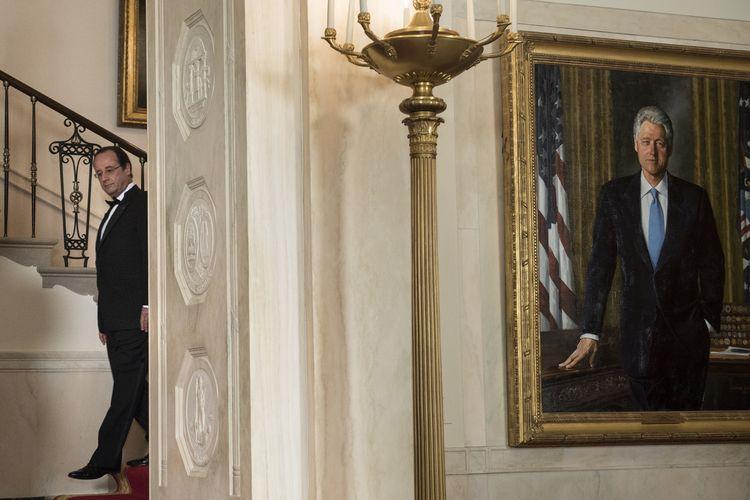 Presiden Perancis Francois Hollande saat tiba di Gedung Putih untuk jamuan makan malam pada 11 Februari 2014. Ia difoto bersama potret eks Presiden Amerika Serikat Bill Clinton.