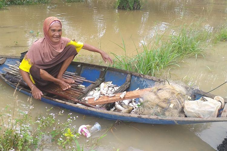 Kartini menepikan perahunya setelah mendapatkan ikan yang banyak di tengah banjir yang melanda wilayah tempat tinggalnya di Desa Sontang, Kecamatan Bonai Darussalam, Kabupaten Rohul, Riau, Sabtu (30/11/2019).