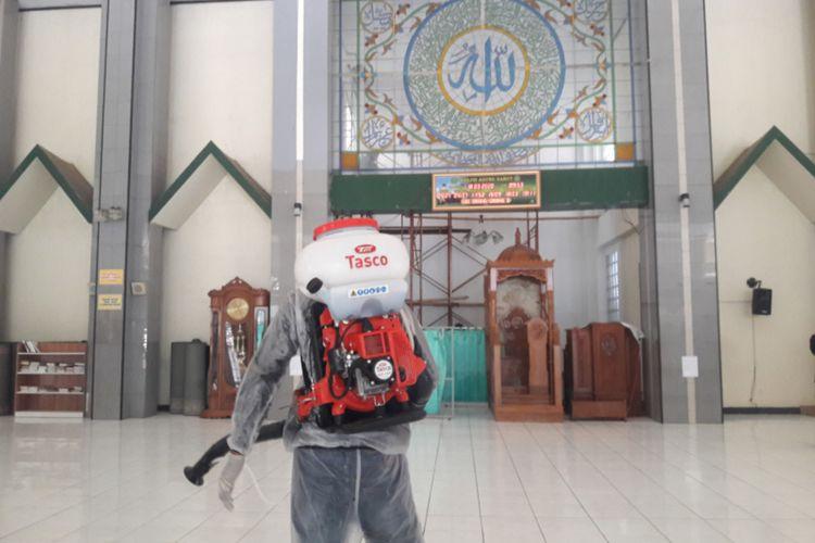 Seorang petugas penyemprot pembasmi hama Dinas Pertanian Garut menyemprotkan disinfektan ke lantai Masjid Agung Garut, Rabu (18/03/2020)