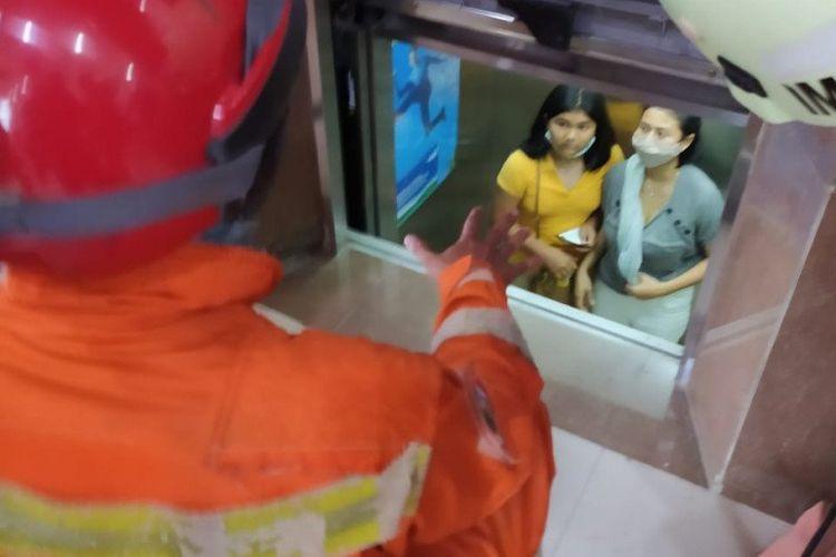 Petugas penyelamatan dari Damkar Jakarta Selatan mengevakuasi ibu dan dua anak yang terjebak di dalam lift gedung Kimia Farma, Grogol Selatan, Jakarta Selatan, Sabtu (31/10/2020).