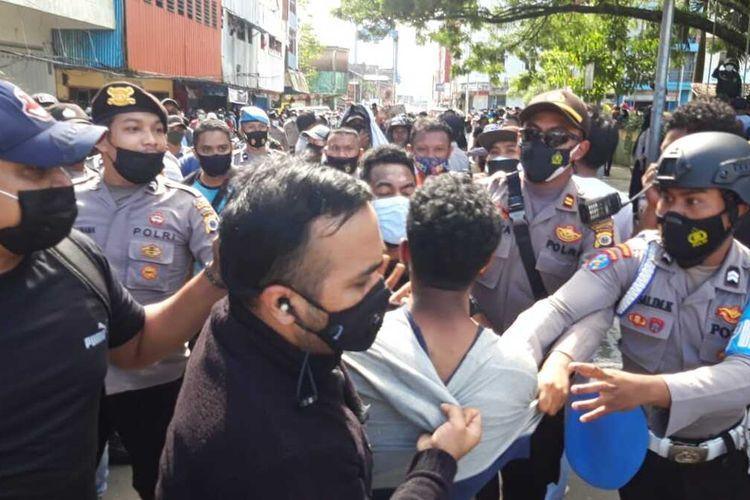 Aparat kepolisian menangkap sejumlah mahasiswa saat aksi unjuk rasa menolak penerapan pembatasan kegiatan masyarakat (PPKM) di depan kantor Wali Kota Ambon berujung bentrok, Jumat (16/7/2021)