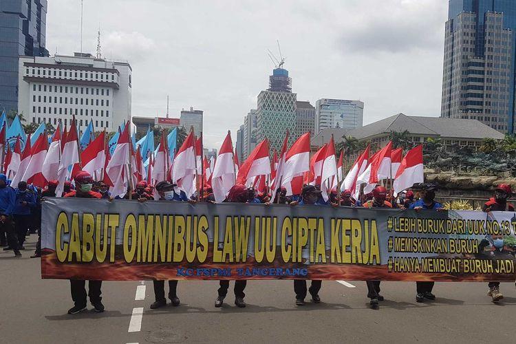 Massa Buruh Membawa spanduk yang menyerukan penolakan pada Omnibus Law UU Cipta kerja, pada aksi unjuk rasa, Senin (2/11/2020) di sekitar Patung Kuda Arjuna Wiwaha, Jakarta Pusat.
