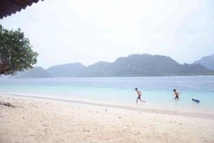 Keceriaan pengunjung saat menikmati keindahan alam dan kejernihan air di Pulau Pagang.