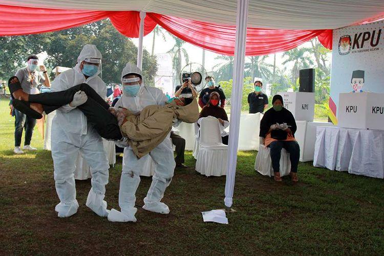 Petugas Kelompok Penyelenggara Pemungutan Suara (KPPS) dengan menggunakan alat pelindung diri (APD) lengkap mengevakuasi pemilih yang pingsan saat akan melakukan pencoblosan ketika Simulasi Pemungutan Suara dengan Protokol Kesehatan Pencegahan dan Pengendalian COVID-19 pada Pilkada Serentak 2020, di TPS 18 Cilenggang, Serpong, Tangerang Selatan, Banten, Sabtu (12/9/2020). Simulasi ini dilaksanakan dengan tujuan untuk memberikan pembelajaran kepada pemilih dalam melaksanakan pemungutan suara Pilkada Serentak 2020 ditengah pandemi COVID-19.
