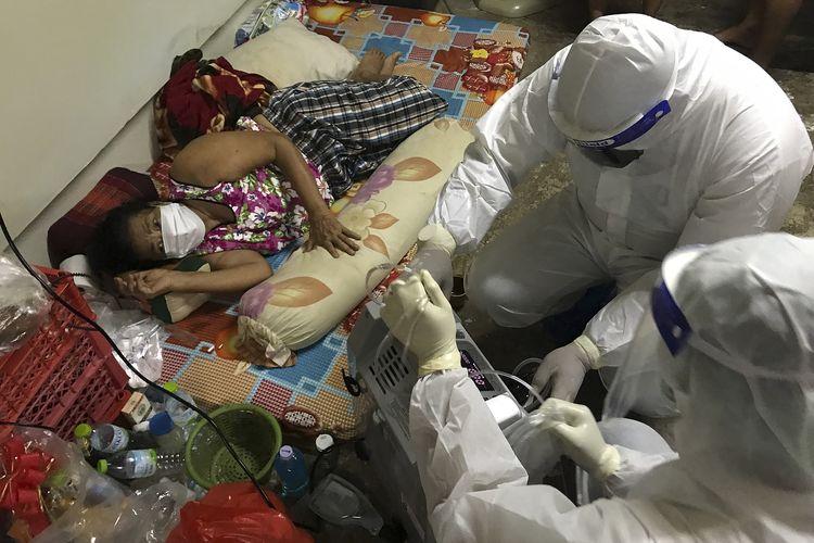 Relawan dari kelompok Saimai Will Survive memakai APD untuk memasang oksigen bagi wanita pasien Covid-19 di Bangkok, Thailand, 23 Juli 2021. Akibat faskes yang kewalahan, warga berinisiatif saling membantu merawat sesama meski harus membahayakan kesehatan sendiri.