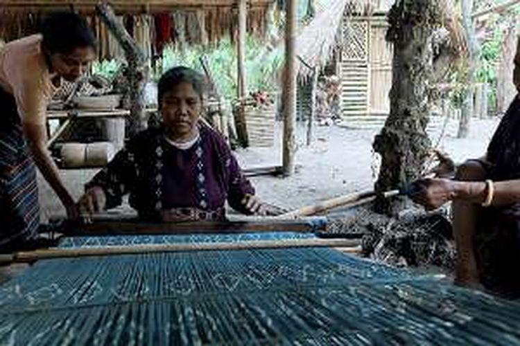 Tiga ibu menyelesaikan pembuatan kain tenun dengan cara tradisional di sanggar tenun ikat pimpinan Alfonsa Horeng, di Nita Pleat, Desa Nita, Kabupaten Sikka, Kamis (4/8/2016). Sanggar ini menjadi wadah ibu-ibu penenun tradisional yang tinggal di sekitar tempat itu.