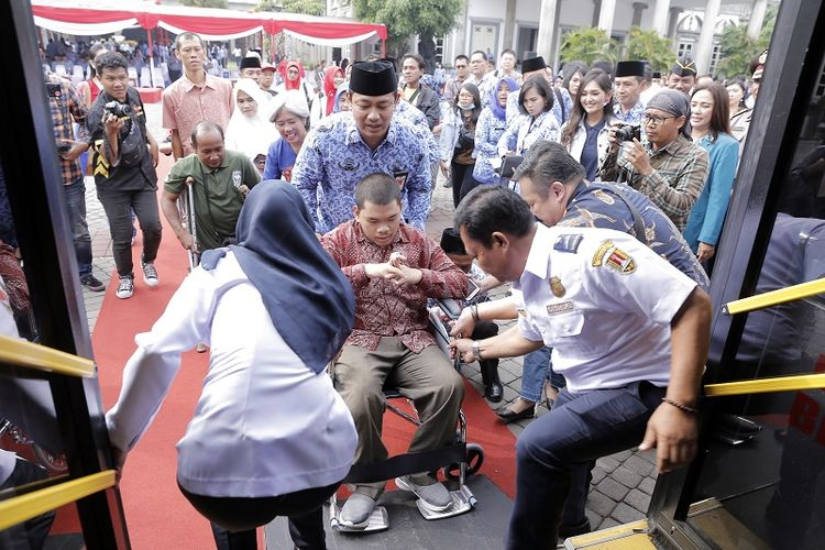Wali Kota Semarang Hendrar Prihadi mendorong kursi roda penyandang difabel menuju bus tingkat wisata Si Kuncung pada peringatan 3 tahun kepemimpinannya di halaman Balai Kota Semarang, Senin (18/2/2019).