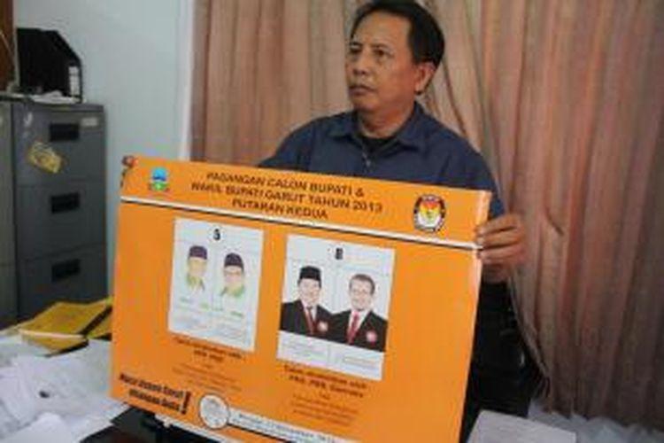 Anggota KPUD Garut menunjukkan Banner berisi foto pasangan calon bupati Garut yang akan maju pada Pilkada putaran kedua , Minggu (17/11/2013) mendatang.