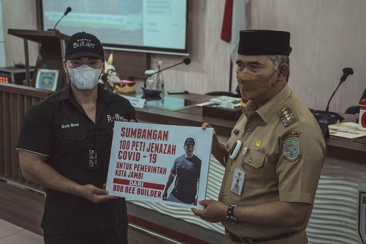 Bob Bee Builder saat menyerahkan 100 peti mati kepada Wali Kota Jambi Syarif Fasha di Aula Kantor Wali Kota Jambi, Selasa (3/8/2021).