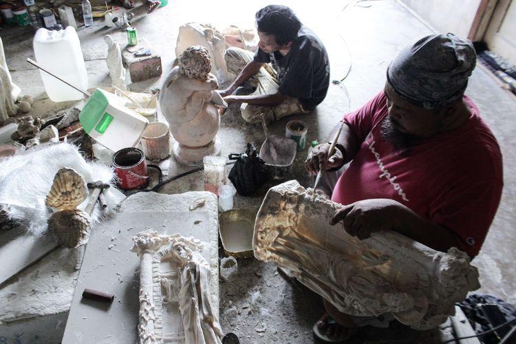 Pekerja menyelesaikan pembuatan patung rohani yang diproduksi oleh pabrik rumahan di Lekong, Serpong, Tangerang Selatan, Senin (23/12/2019). Sedikitnya, dalam satu hari bengkel tersebut harus menyelesaikan 10 patung dengan besaran 60 sentimeter dan satu patung berukuran tiga meter.