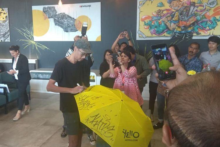 Perupa Indonesia Stereoflow saat melukis grafiti di oermukaan payung.