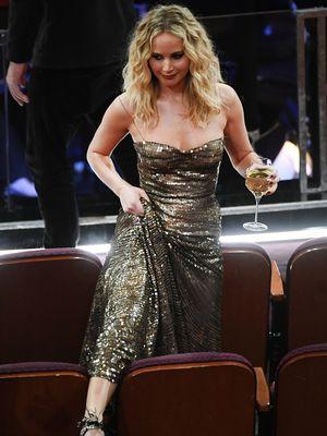 Jennifer Lawrence melompati kursi di ruang Dolby Theatre tempat Academy Awards ke-90 digelar di Hollywood, California, Minggu (4/3/2018).
