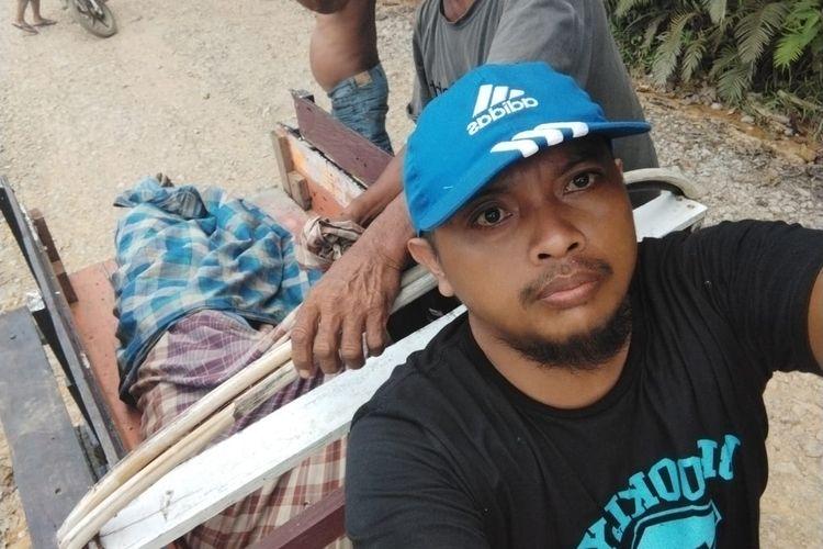 Warga bernama Andi Muhammad Hatta (39) saat menyetir gerobak motor saat mengevakuasi jenazah pria lanjut usia di Kelurahan Sepaku, Kabupaten PPU, Kaltim, Minggu (12/9/2021).