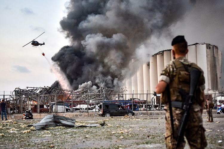 Petugas berjaga saat helikopter memadamkan api di lokasi ledakan di kawasan pelabuhan di Beirut, Ibu Kota Lebanon, Selasa (4/8/2020). Sebanyak 73 orang tewas dan ribuan lainnya dilaporkan terluka dari insiden dua ledakan besar yang mengguncang Beirut tersebut.