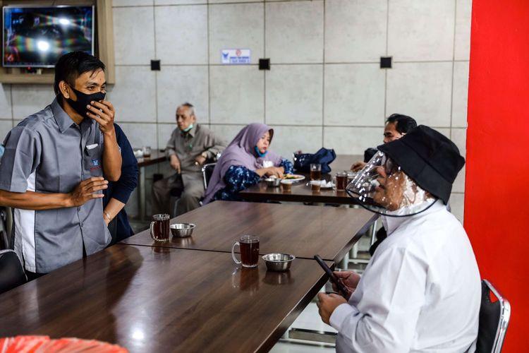 Pelayan menggunakan masker saat melayani pengunjung di Restoran Sederhana, Bendungan Hilir, Jakarta Pusat, Senin (8/6/2020). Sebagai bagian dari rencana penerapan kenormalan baru 8 Juni 2020, pemerintah DKI Jakarta mengharuskan pengusaha rumah makan membatasi kapasitas maksimal 50 persen, larangan penyajian makanan secara prasmanan dan tetap menerapkan protokol kesehatan.
