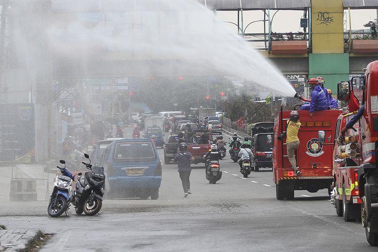 Petugas pemadam kebakaran menyemprotkan cairan disinfektan di jalan Margonda Raya, Depok, Jawa Barat, Senin (23/3/2020). Penyemprotan disinfektan di jalan protokol dan fasilitas umum di kota tersebut guna mencegah penyebaran virus corona atau COVID-19.