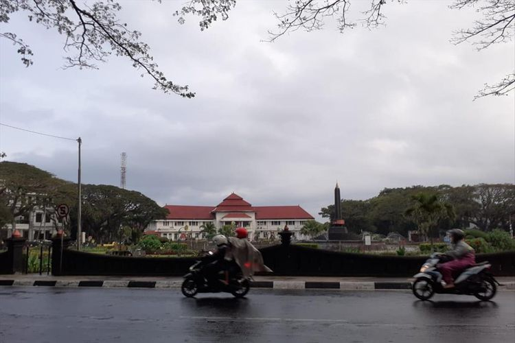 Pengendara melintas di Bundaran Tugu Kota Malang saat turun gerimis, Jumat (5/7/2019)