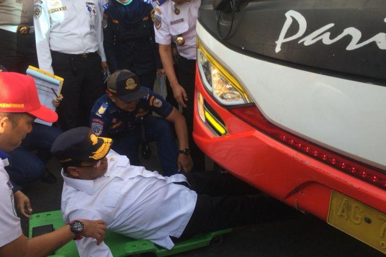 Menhub Budi Karya Sumadi masuk ke dalam kolong bus mengecek rem bus pariwisata yang parkir di area taman wisata Tawangmangu, Kabupaten Karanganyar, Jawa Tengah, Kamis ( 27/12/2018).