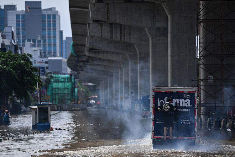 Seorang pria naik ke bagian belakang sebuah truk untuk melintasi banjir di Jalan Boulevard Barat Raya, Kelapa Gading, Jakarta Utara, Minggu (23/2/2020). Hujan deras sejak Minggu 23 Februari dini hari membuat sejumlah daerah di Ibu Kota tergenang banjir.