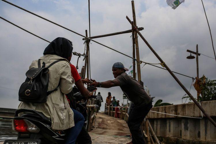 Warga menggunakan jasa penyeberangan perahu kayu eretan untuk menyebrang Kali Cegak di Kapuk Muara, Penjaringan, Jakarta Utara, Selasa (12/2/2019). Satu kali penyeberangan pengendara motor harus membayar tarif Rp 2.000, jika berboncengan tarifnya Rp 3.000. Sedangkan bagi pejalan kaki, sepeda, dan gerobak kecil dikenai tarif Rp 1.000.