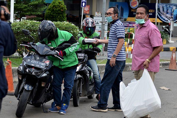 Relawan organisasi Pelmas BPD Bekasi GBI bersama Tagana Rajawali membagi-bagikan makan siang gratis kepada pengemudi ojek online (ojol) di Bekasi, Jawa Barat, Kamis (2/4/2020). Pembagian makan gratis sebagai bentuk kepedulian terkait pendapatan dan orderan pengemudi ojol yang menurun akibat wabah COVID-19.