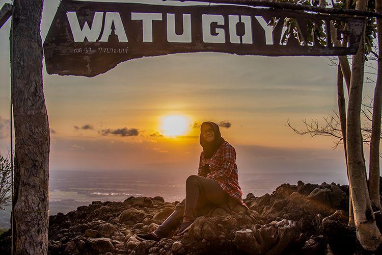 Seorang pengunjung berfoto dengan latar belakang matahari terbanam di Watu Goyang, Bantul, Yogyakarta