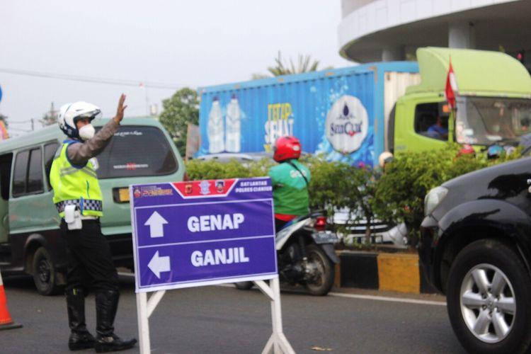 Seorang anggota polisi sedang mengatur kendaraan di bundaran Tugu Lampu Gentur Cianjur, Jawa Barat, Jumat (3/9/2021) menyusul pemberlakuan sistem ganjil genap di kawasan Puncak hari ini.