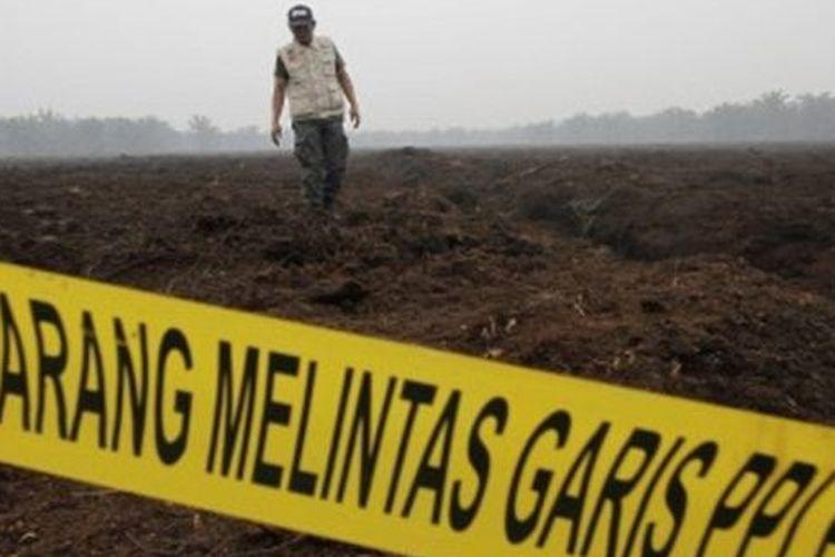Petugas Ditjen Penegakan Hukum Kementerian Lingkungan Hidup dan Kehutanan (KLHK) berjalan usai menyegel lahan perusahaan asal Malaysia PT Adei Plantation and Industry di Kabupaten Pelalawan, Riau, Jumat (13/9/2019).