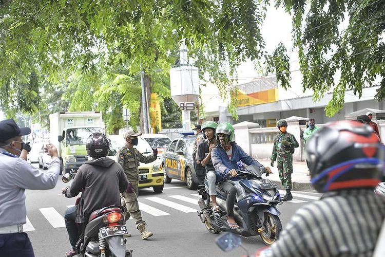 Petugas gabungan dari TNI, Polri, Polisi Pamong Praja DKI Jakarta dan Dsihub melakukan imbauan kepada pengendara motor untuk dapat mematuhi penerapan Pembatasan Sosial Berskala Besar (PSBB) di jalan cempaka putih raya, Cempaka Putih, Jakarta (11/4/2020). Iimbauan ini dilakukan agar masyarakat menerapkan pembatasan sosial berskala besar (PSBB) selama 14 hari, yang salah satu aturannya adalah pembatasan penumpang kendaraan serta anjuran untuk menggunakan masker jika berkendara.