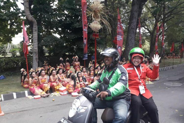 Wali Kota Surabaya Tri Rismaharini menumpangi ojek online ketika menghadiri Kongres Partai Demokrasi Indonesia Perjuangan di Hotel Grand Inna Bali Beach, Sanur, Kamis (8/8/2019).