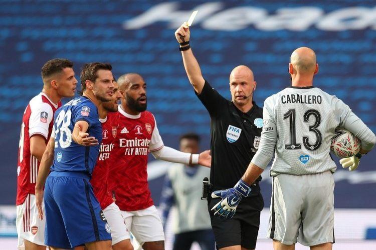 Wasit Anthony Taylor memberikan kartu kuning kepada Cesar Azpilicueta pada laga final Piala FA 2019-2020 antara Arsenal dan Chelsea.