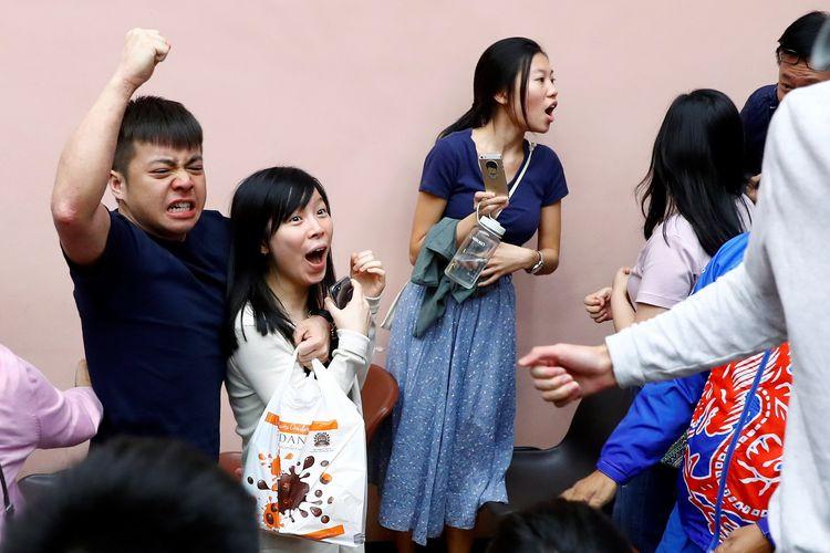 Pendukung dari kandidat lokal Kevin Lam merayakan kemenangan mereka di distrik South Horizons West Hong Kong, pada 25 November 2019. Kelompok pro-demokrasi Hong Kong menang dalam pemilihan distrik, sekaligus menjadi tamparan keras bagi China.