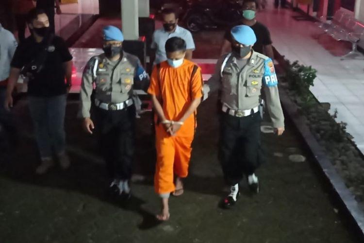 Dua petugas polisi mengawal tersangka RRM di Polres Sukabumi Kota, Sukabumi, Jawa Barat, Jumat (16/10/2020).