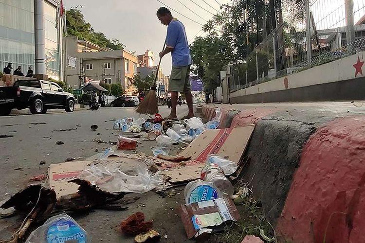 Seorang warga membersihkan sampah seusai berlangsungnya aksi unjuk rasa di Jayapura, Papua, Jumat (30/8/2019). Sejumlah bangunan dan kendaraan terbakar saat aksi unjuk rasa yang berakhir rusuh di Jayapura, Kamis kemarin, masih terkait memprotes dugaan tindak rasisme kepada mahasiswa Papua di Jawa Timur beberapa waktu lalu.