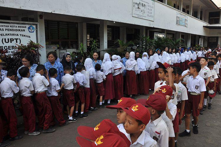 Sejumlah siswa menyalami guru mereka seusai mengikuti upacara di Sekolah Dasar Negeri 060813 Medan, Sumatera Utara, Senin (25/11/2019). Menyalami guru oleh para siswa tersebut dalam rangka memperingati Hari Guru yang serentak dilaksanakan di seluruh Indonesia.