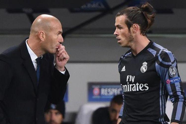 Pemain Real Madrid, Gareth Bale (kanan), sedang mendengarkan instruksi dari pelatihnya, Zinedine Zidane, dalam partai Liga Champions kontra Legia Warsawa, di Pepsi Arena, Rabu (2/11/2016).